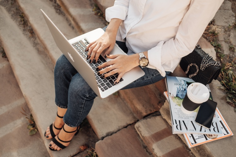 TERNOPIL, UKRAINE - AUGUST 28, 2019: Fashionable Girl with Gucci Handbag Working on Apple Laptop Macbook Air, Freelance Worker, Business Lady Reads Magazine Bazaar and Elle